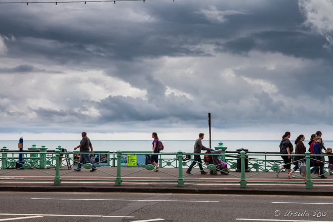 Warmly-dressed people on and ocean-front walkway, under black skies, Kings Rd Brighton, UK