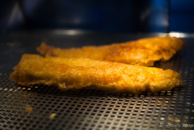 Two pieces of battered fish on a fryer drainboard, Brighton, UK