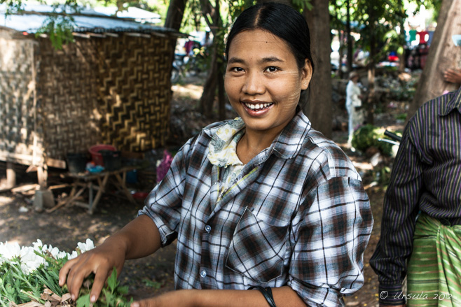 Portrait: Smiling Burmese woman in a black and white checkers shirt,  Pyin Oo Lwin Flower Market, Myanmar.