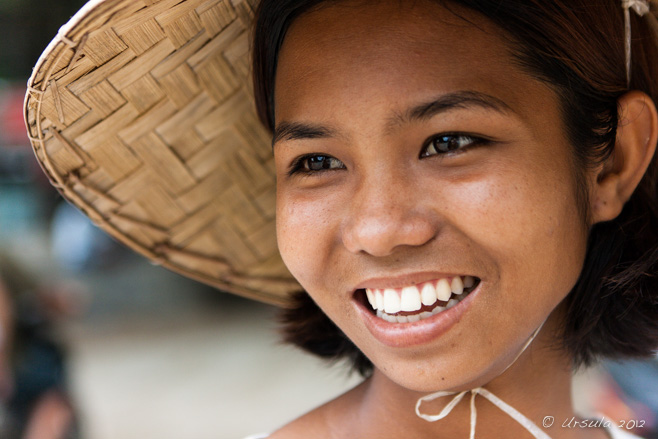 Portrait: Beautiful young smiling burmese woman in a straw bonnet.