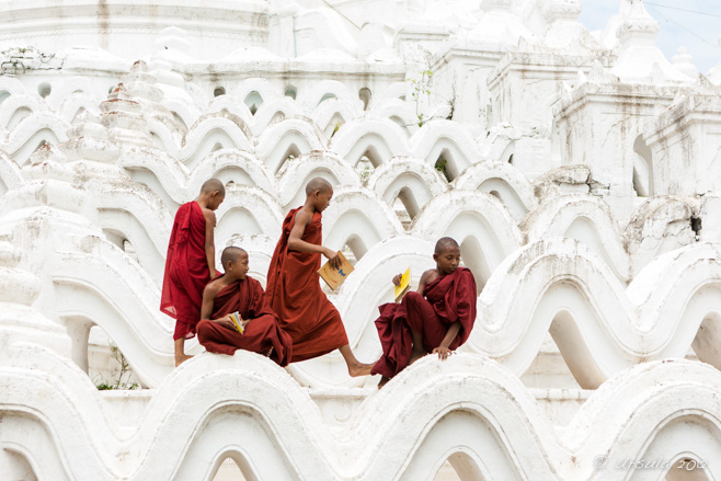 Four young burmese novice monks arrange themselves on the terraces of Hsinbyume Pagoda, Mingun, Myanmar.