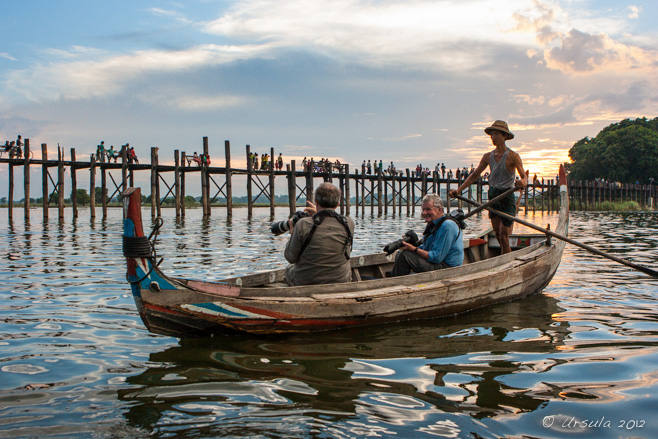 Standing boatman in a pith-hat and two men seated with large cameras, watching the foot-traffic on U Bein Bridge, Amarapura, Myanmar