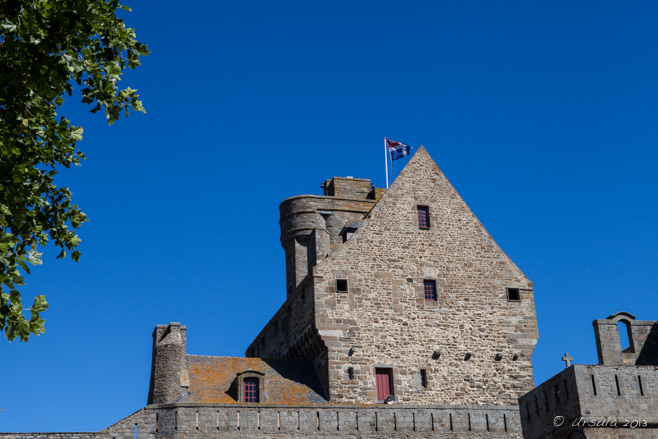 Medieval buildings over a city wall, against a blue sky, flying a French flag. Saint-Malo, Bretagne