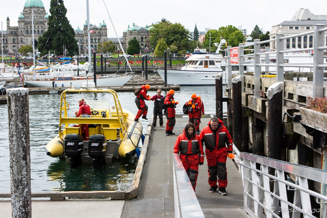 A yellow Zodiak in Victoria Harbour; people in red Mustang Survival flotation suits.