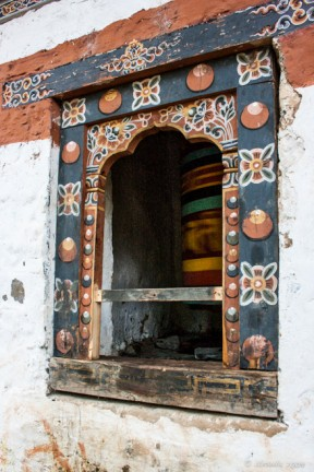 A spinning Bhutanese prayer wheels inside a colourfully painted window, Tiger