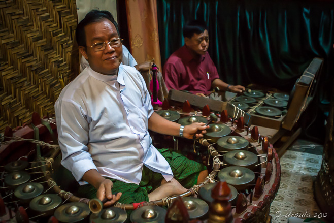 A burmese man playing a range of cymbals, Mandalay Marionette Theatre.