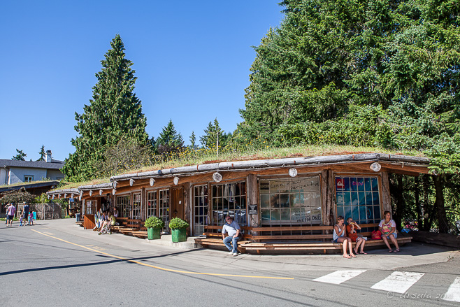 People sit outside the wooden buildings of the Coombs Country Market, BC