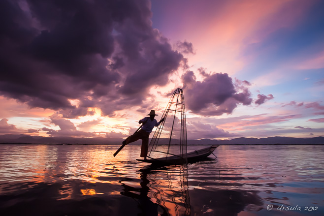Sunset silhouette of a leg-rowing fisherman, Inle Lake Myanmar