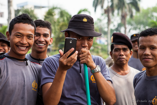 Indonesian policeman taking a photo with a mobile phone, Maimoon Palace, Medan