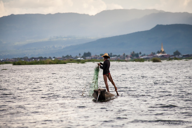 A leg-rowing fisherman ready to cast his net, Inle Lake, Myanmar