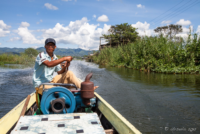 Burmese man on the controls of a longtail boat, Inle Lake, Myanmar