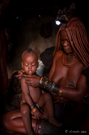 Himba Mother and Child in a dark hut, Kunene Region Namibia