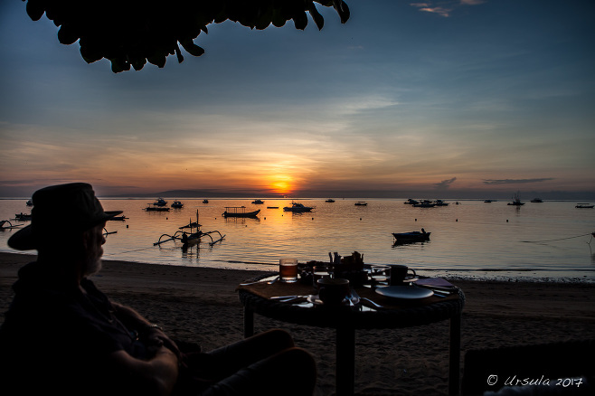Silhouette of a seated man at sunrise, Sanur Beach Bali
