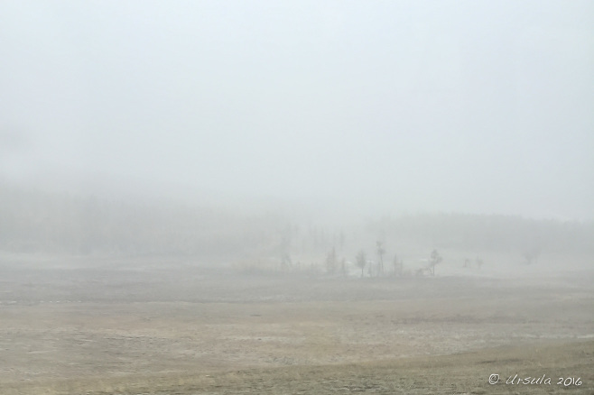 View through fog and snow over open barren Mongolian steppes.