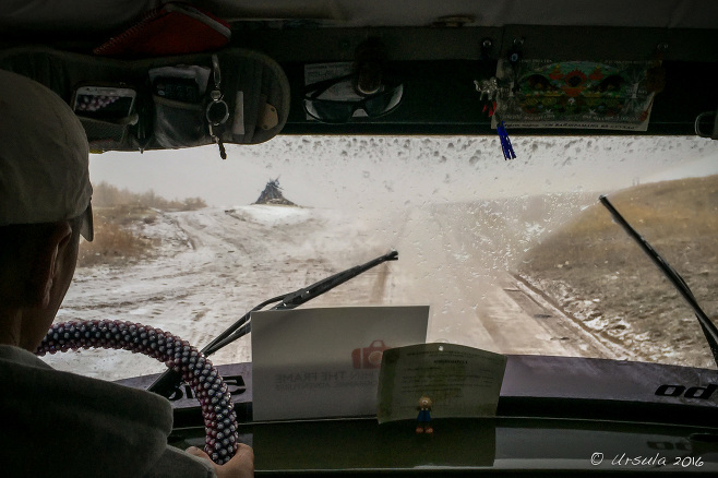 View from a UAZ windscreen over a snowy dirt road in Western Mongolia.