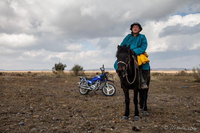 Nomad on the Horseback with a motorcycle in the background, Uvs Province Mongolia