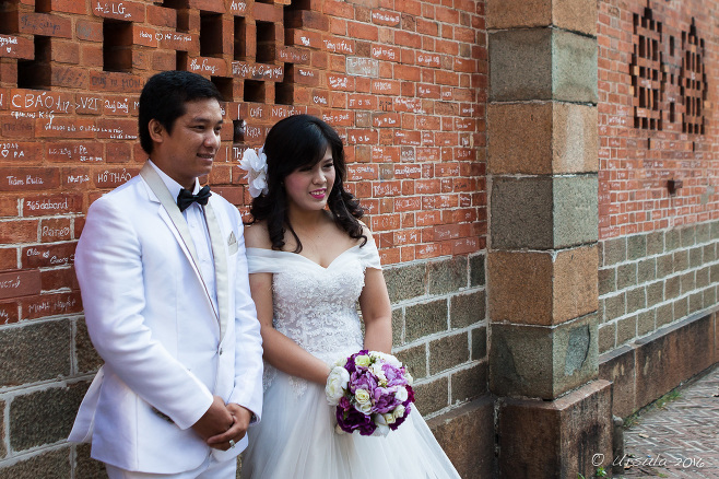 Vietnamese Wedding Couple in white in font of a red brick wall of Notre Dame Cathedral, Ho Chi Minh City Vietnam