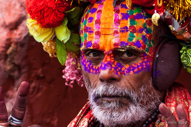 Portrait: bearded man in elaborate face paint, tinsel, artificial flowers, and pompoms, Pashupatinath Nepal