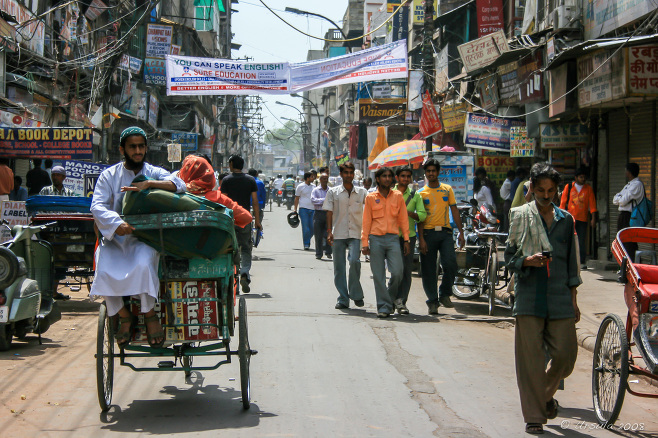 Pedestrians and cycle-rickshaws in a Chandni Chowk Street, Old Delhi, India.