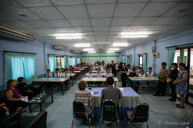 Fluorescent-lit Department of Education Office with students waiting at tables, Mae Sariang Thailand