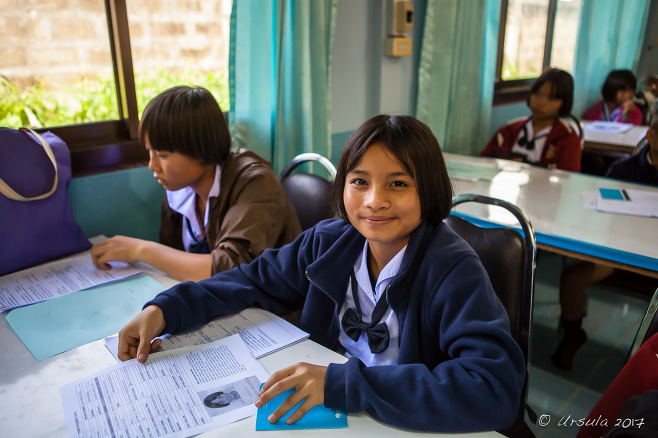 Karen schoolgirl in a Department of Education Office with students waiting at tables, Mae Sariang Thailand