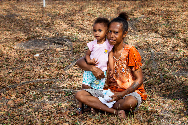 Papuan Mother seated in grass with her toddler, Port Moresby, Papua New Guinea